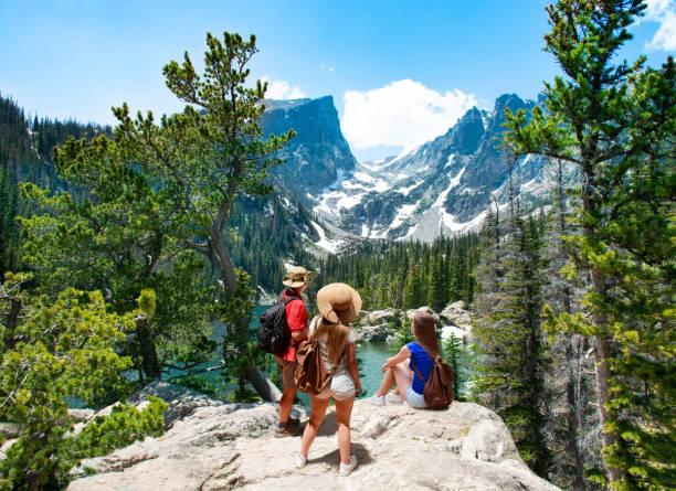 Family standing on top of the mountain enjoying  beautiful scenery. stock photo