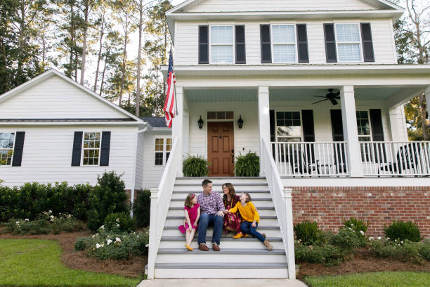 family standing outside front of new construction white siding farmhouse in the suburbs - casa imagens e fotografias de stock