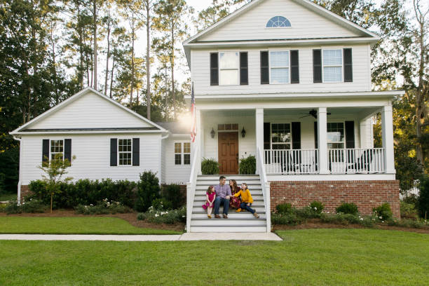 Family standing outside front of new construction white siding farmhouse in the suburbs Family sitting outside on the steps of a new construction white siding farmhouse in the suburbs outdoors stock pictures, royalty-free photos & images