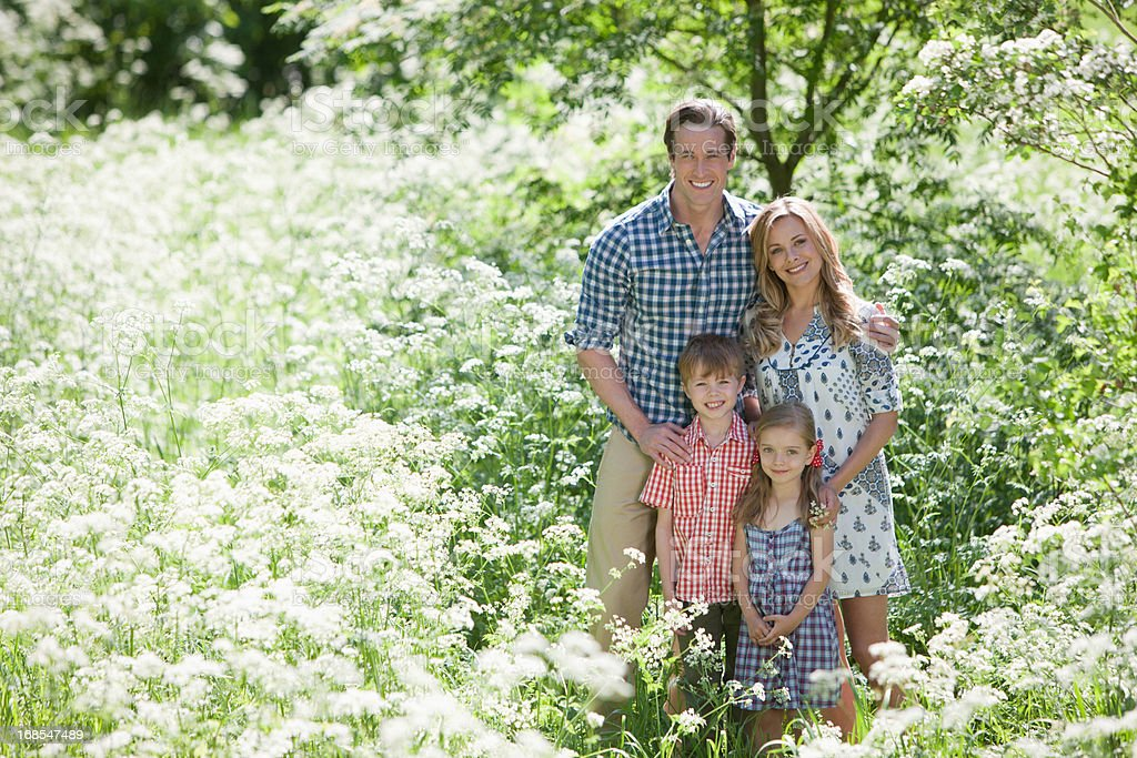 Family standing together in field of flowers royalty-free stock photo