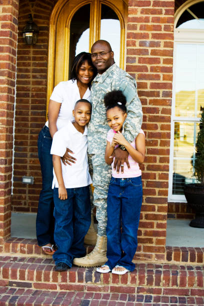 A family standing together on the front steps of their home stock photo