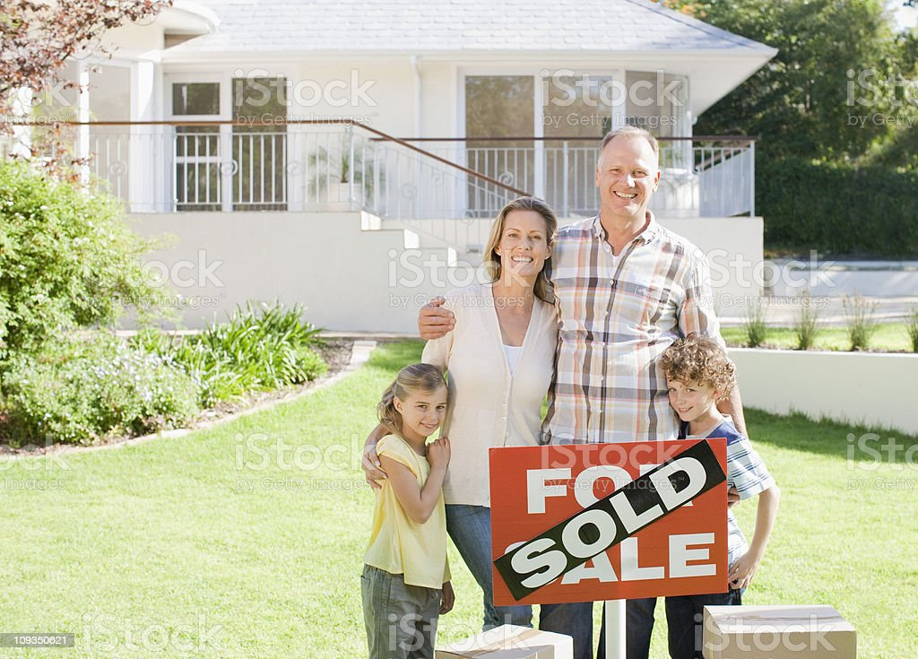 Family standing with sold sign of their new house royalty-free stock photo