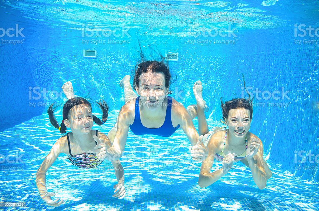 Family swim in pool underwater, mother and children under water stock photo