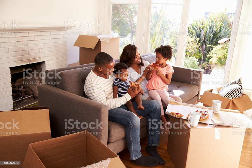 Family Take A Break On Sofa With Pizza On Moving Day stock photo