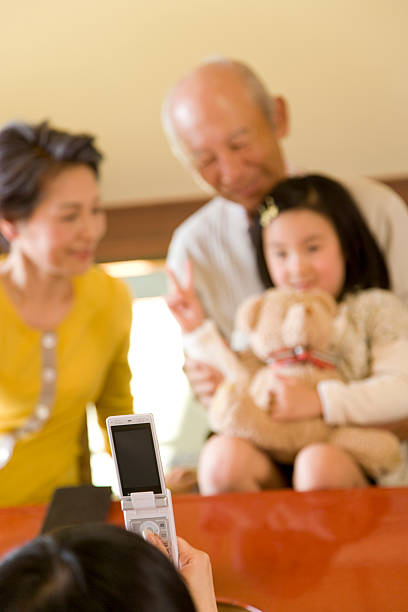 Family taking a ceremonial photograph with mobile phone stock photo