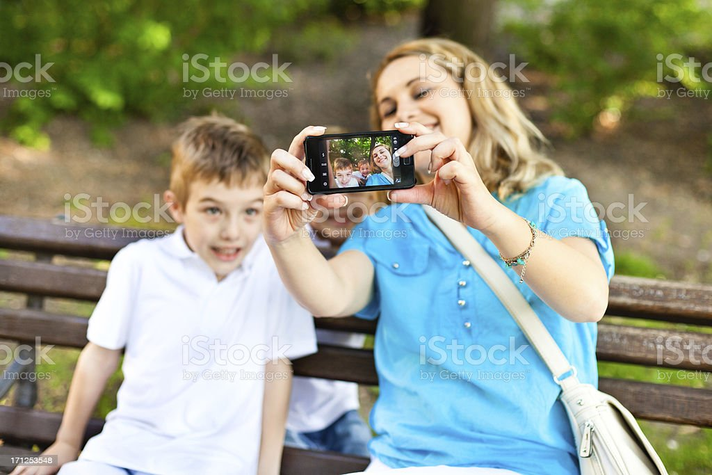 Family taking a photo of themselves with cellphone royalty-free stock photo