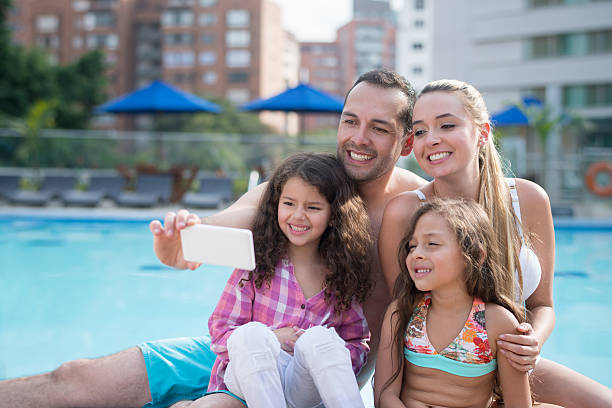 Family taking a selfie by the pool stock photo