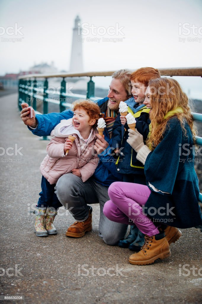 Family Taking a Selfie with their Ice-Cream Cones on the Coast stock photo