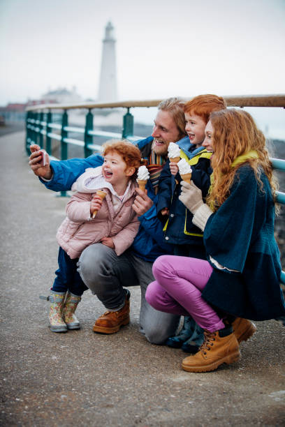 Family Taking a Selfie with their Ice-Cream Cones on the Coast Young redheaded family enjoying eating ice-cream on the coast. Its cold outside so they are wrapped up warm. They kneel down with the children in front of  railings and smile while the man takes a selfie of them all northeastern england stock pictures, royalty-free photos & images