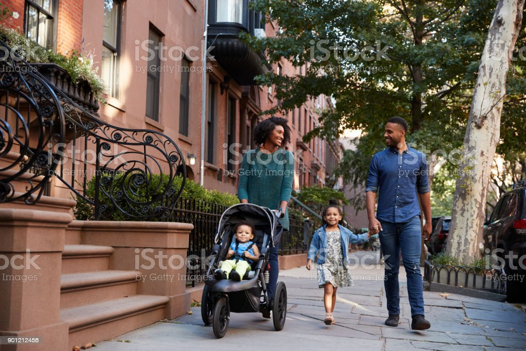 Family taking a walk down the street stock photo