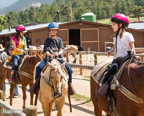 Middle aged woman and her son and daughter taking a horseback riding lesson in Colorado