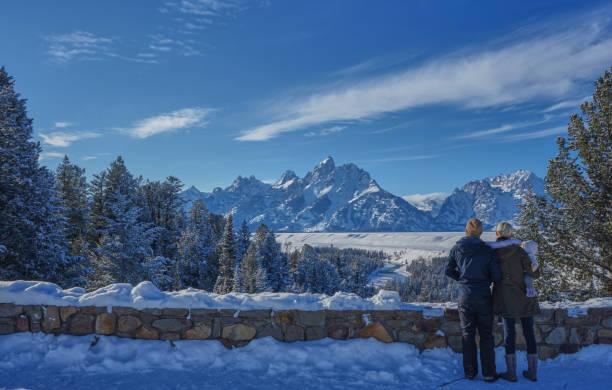 Family Taking in the View in the Winter at Christmas in the Grand Tetons National Park and Yellowstone National Park USA stock photo
