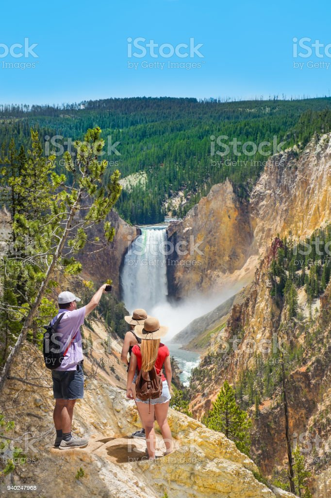 Family taking photos of beautiful waterfall with phone. stock photo