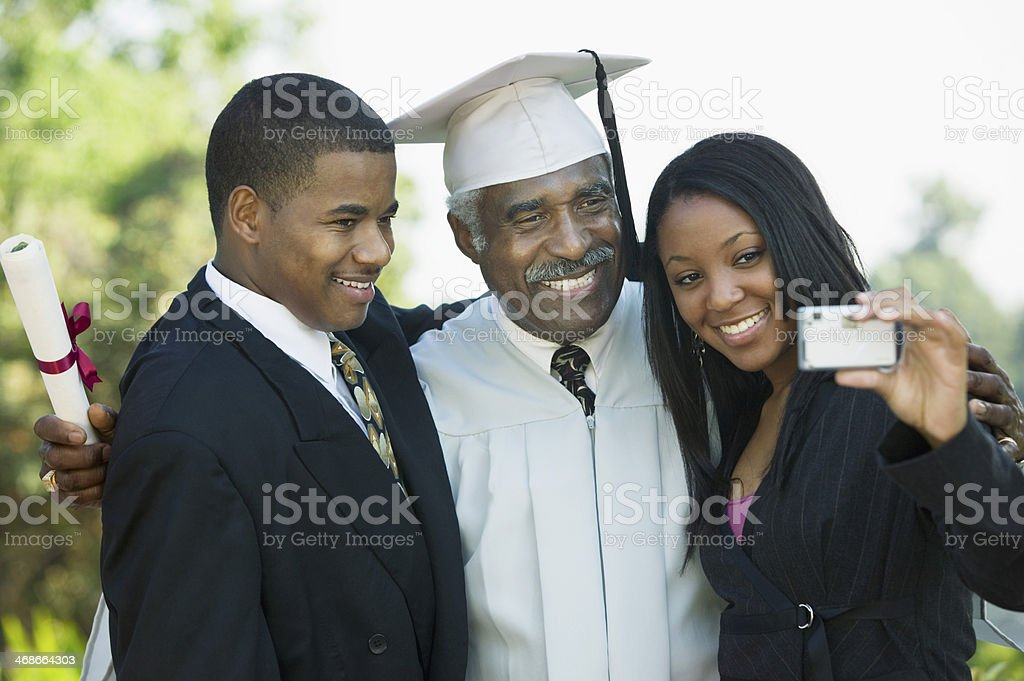Family Taking Picture at Graduation with Cell Phone stock photo