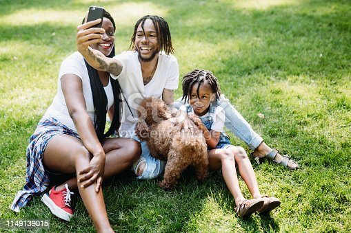A cute young African American family enjoys relaxation time in a city public park with their pet poodle.   They take a self portrait with their smart phone.  Shot in Tacoma, Washington.