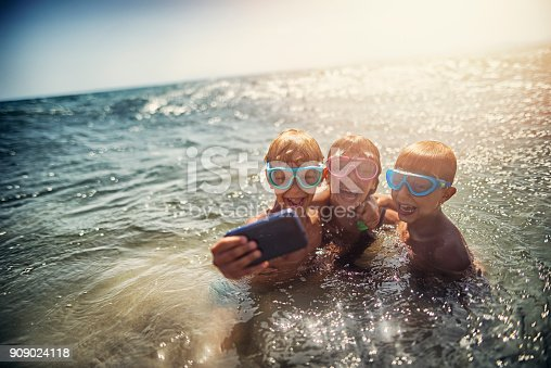 Mother and three kids are sitting on a Benalmadena beach in the evening. They are taking selfies on last day of the summer vacations. Andalusia, Spain.