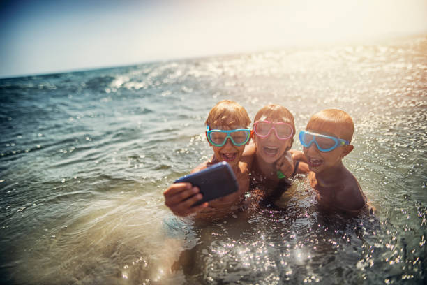 Family taking selfie on a beach in the evening stock photo