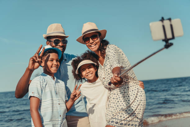 family taking selfie on beach - family vacation stock photos and pictures