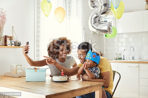 Smiling woman taking selfie with man and boy at table. Parents are sitting with son in kitchen. Family is making memories while celebrating birthday at home.