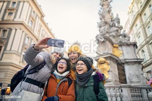 Mother and kids sightseeing Vienna. The family is taking selfies near Column of Pest monument (Wiener Pestsäule).