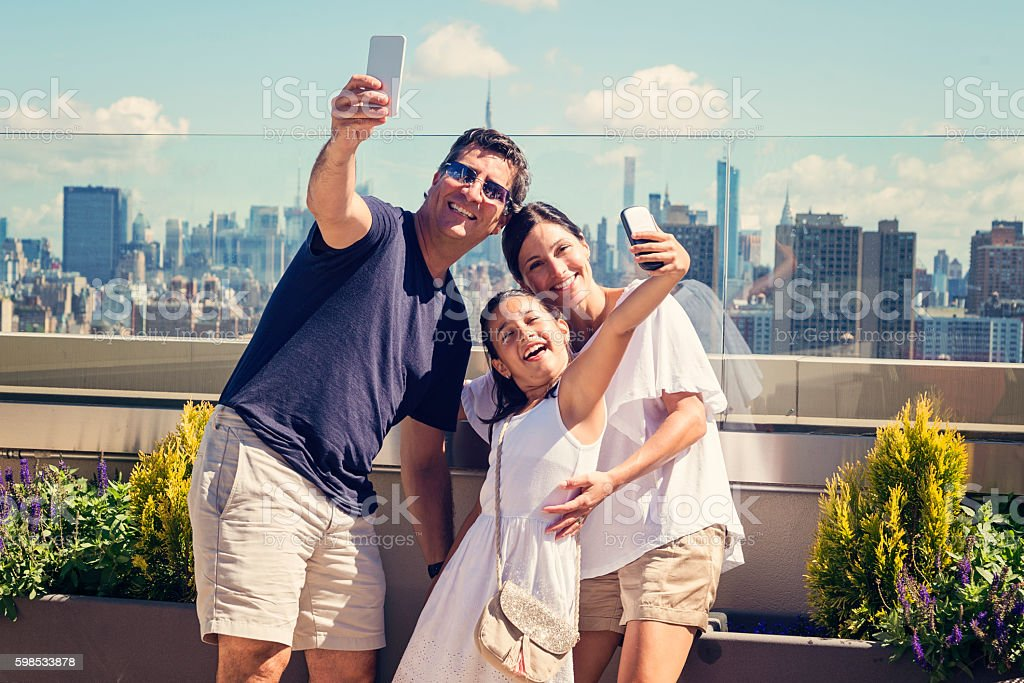Family taking selfies on a rooftop with New-York skyline. photo libre de droits