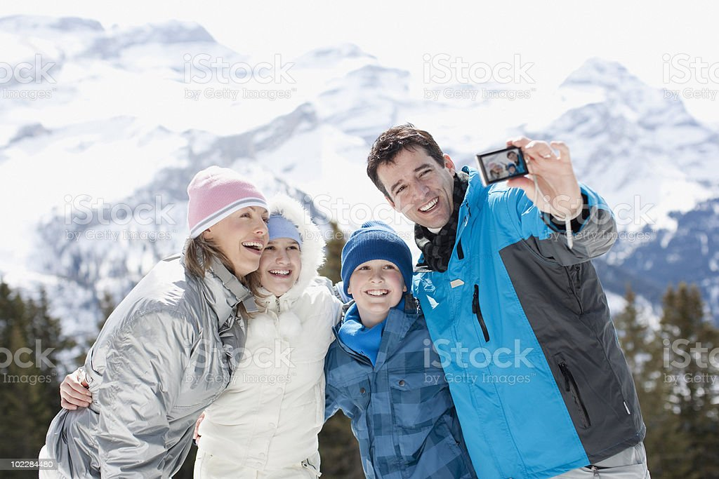 Family taking self-portrait in snow royalty-free stock photo