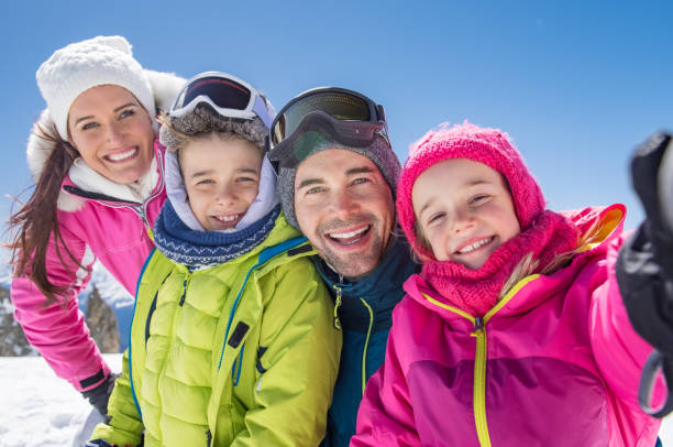 Family taking winter selfie Happy family taking selfie in snowy mountain during winter holiday. Daughter taking a picture of family on the alps while looking at camera. Happy mother and father with children posing for a selfie. ski holiday stock pictures, royalty-free photos & images