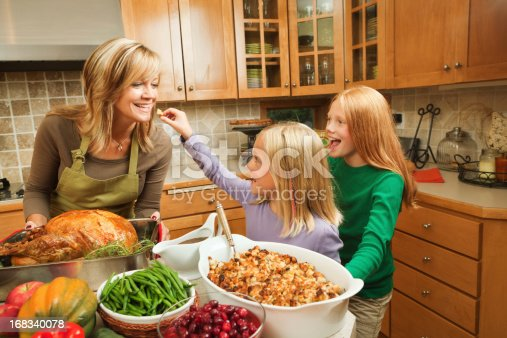 Family Thanksgiving holiday celebration preparation with mother and two daughters cooking turkey dinner together in a residential home domestic kitchen. One happy child assists, playfully holding up a morsel for her smiling parent to taste, while the other offspring girl cheers. The abundant, hearty fall meal is a USA tradition.