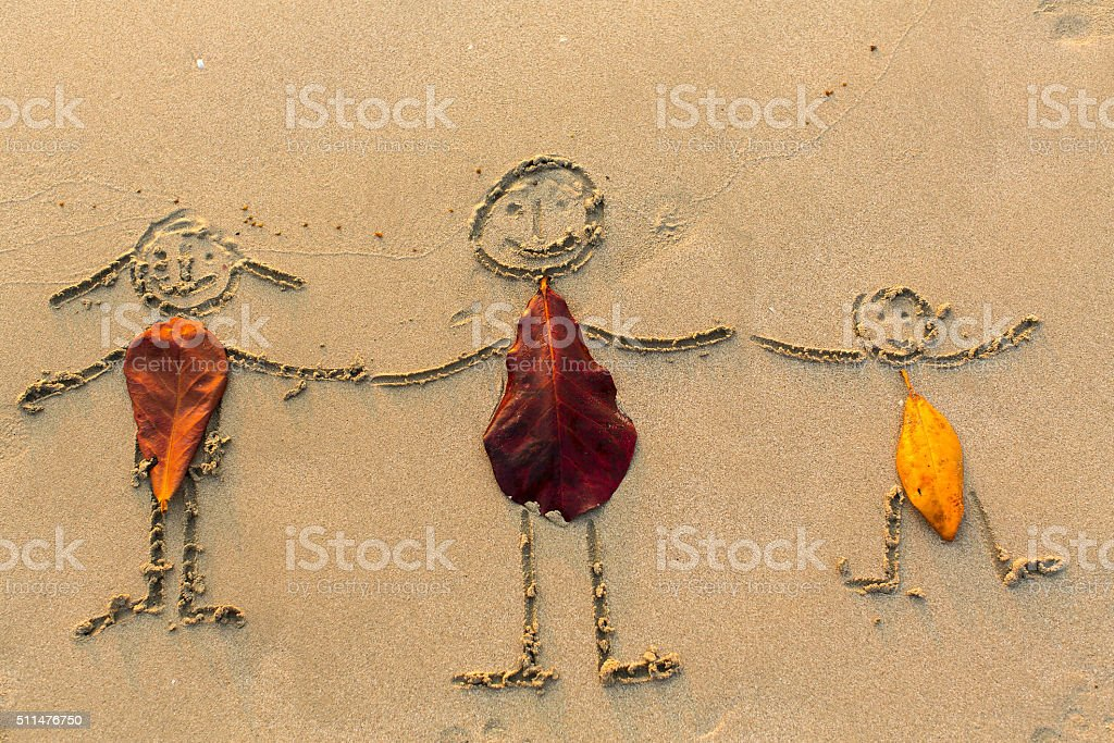 Family, three people drawn on the beach sand. stock photo