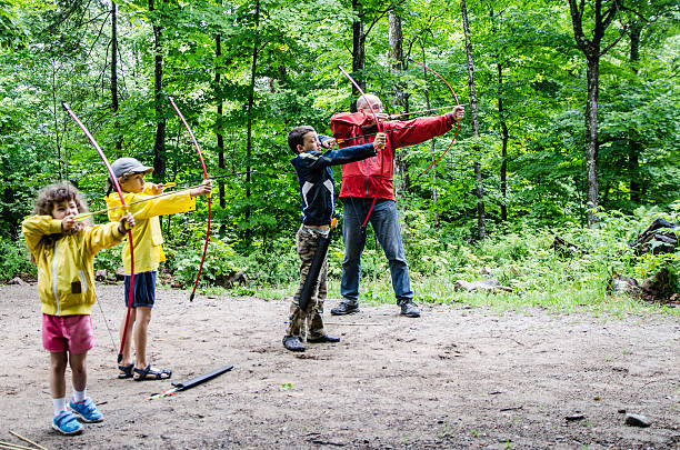 famille jeter des flèches à la cible - tir à l'arc photos et images de collection