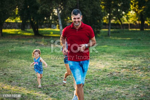 Young caucasian heterosexual parents playing with their daughter in a public park.