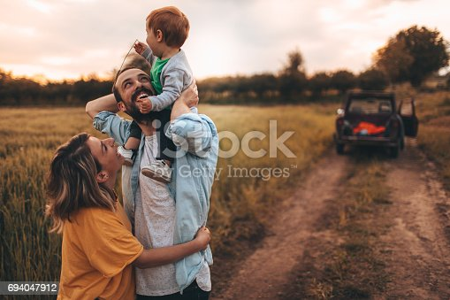 Photo of young family spending some quality time together outdoors in nature, with their baby boy
