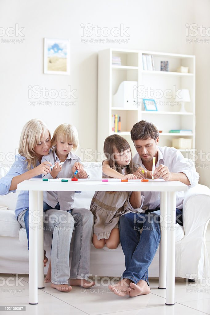 Family time together with parents teaching kids drawing royalty-free stock photo