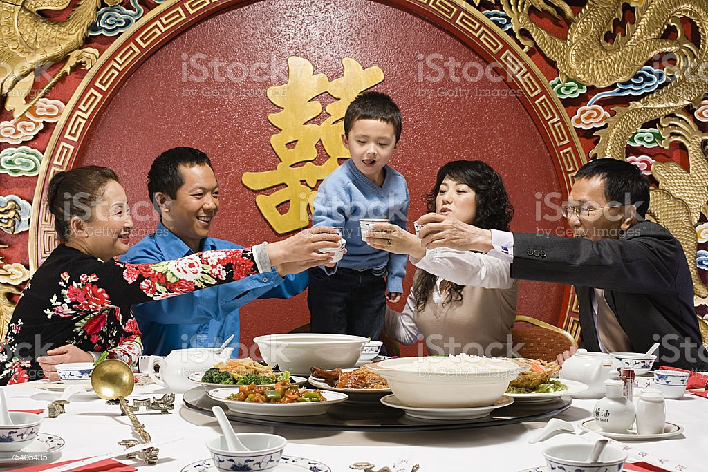 Family toasting at reunion dinner stock photo