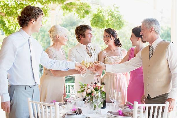 familie beim anstoßen hochzeitsempfang - bräutigam tisch stock-fotos und bilder
