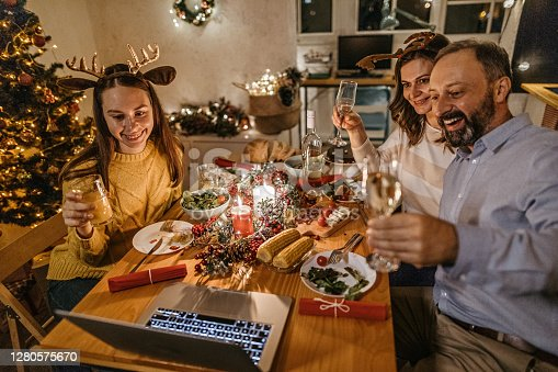 Family toasting drinks on video call using laptop with near and dear ones on occasion of Christmas celebration