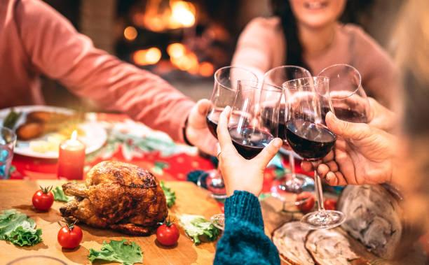 famiglia che brinda al vino rosso e si diverte alla festa di cena di natale - concetto di festa per le vacanze con persone felici che si godono l'inverno insieme a casa cena fest - filtro caldo con focus sui bicchieri - pranzo di natale foto e immagini stock