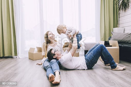istock Family together happy young beautiful with a little baby moves with boxes to a new home 931208350