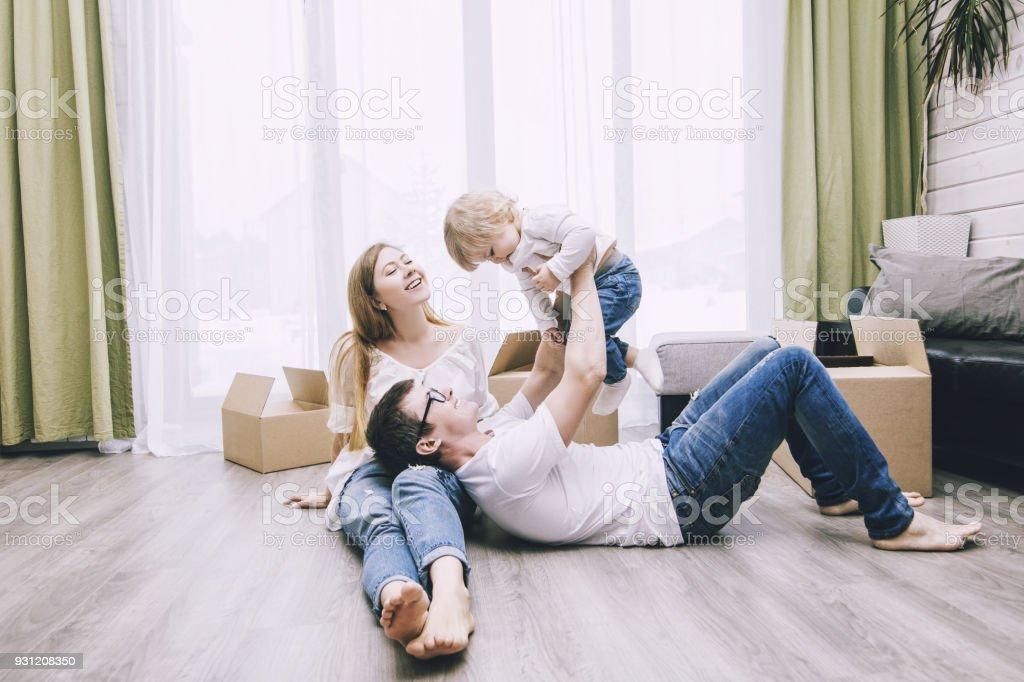Familia junto feliz joven hermosa con un bebé se mueve con las cajas a un nuevo hogar - foto de stock