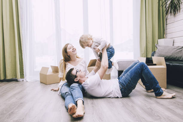 family together happy young beautiful with a little baby moves with boxes to a new home - warm house stock photos and pictures