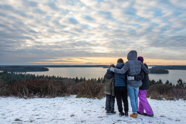 Family together holding each other and looking at a view. Mountain top winter sunset snow scene with water and horizon. stock photo