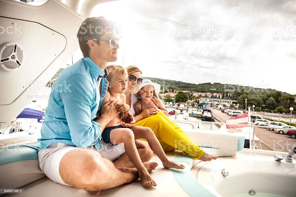 Family together on a boat in summer vacation stock photo