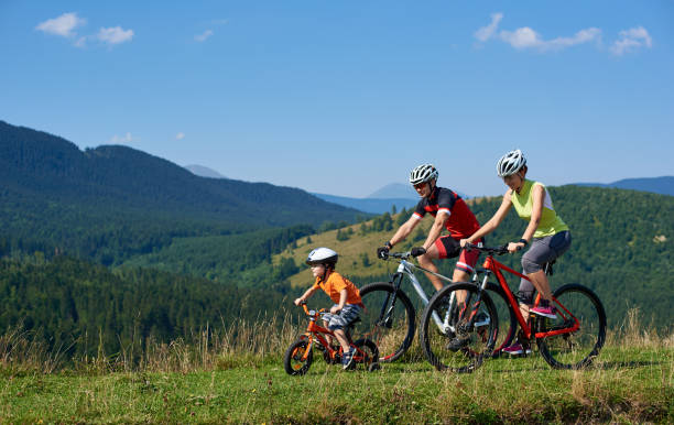 Family tourists bikers, mom, dad and child riding on bicycles on grassy hill - foto stock