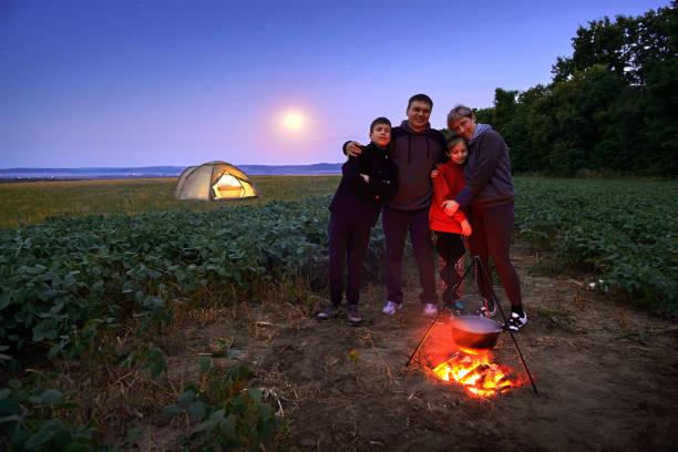 Familia viajando y acampando, crepúsculo, cocinando en el fuego. Hermosa naturaleza - campo, bosque, estrellas y luna. - foto de stock