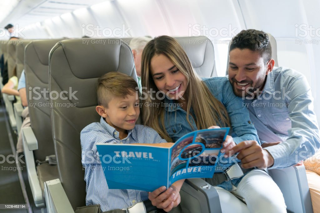 Portrait of a happy family traveling by plane and reading a travel...