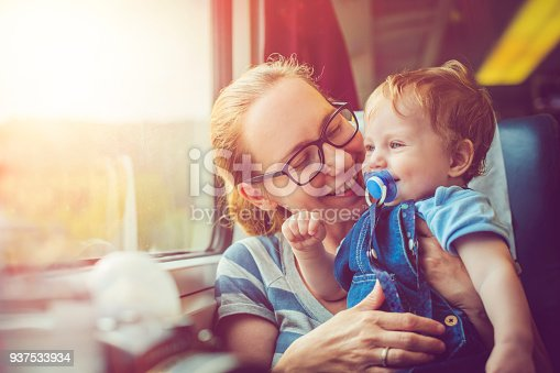 Happy mother and her baby boy travelling in train in summer