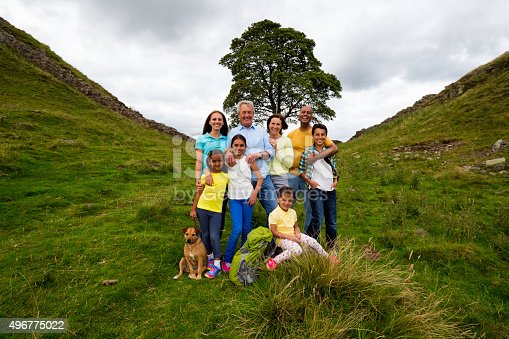 An image of a three generation family posing for a family photograph with their dog past Sycamore gap in the countryside. The ancient tree is surrounded by Hadrian's wall in Northumberland, England. This is a concept shot showing the tree and the three generation family below it.