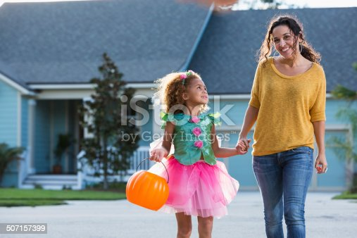 Interracial family - Hispanic mother and mixed race little girl (5 years) going trick or treating on halloween.  Girl is wearing fairy princess costume