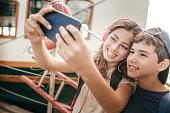 Kids taking selfies on family trip