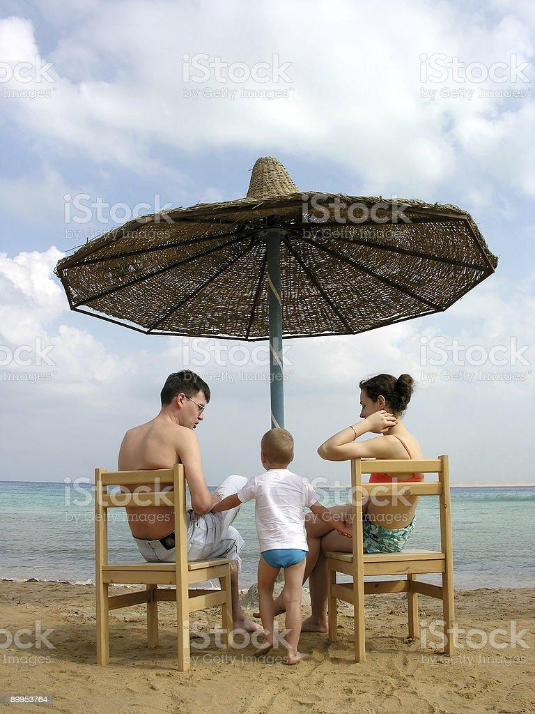 family under umbrella on beach royalty-free stock photo